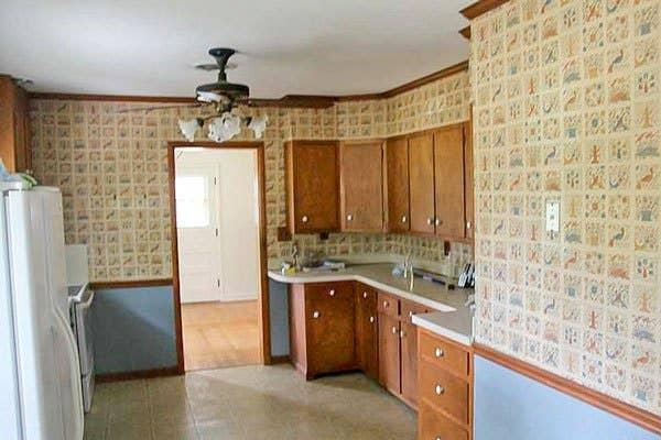 kitchen with blue wallpaper, golden oak cabinets and linoleum flooring