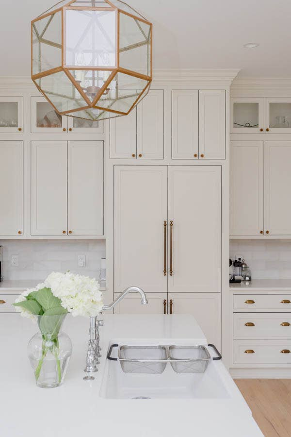 White cabinet front refrigerator with wall of pantry cabinets and counter space