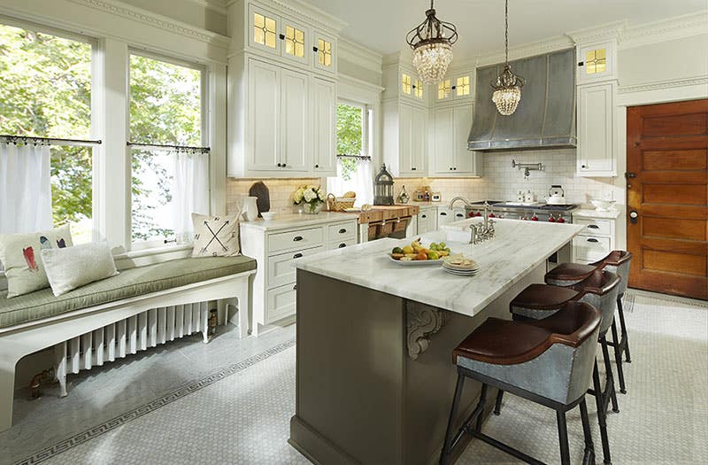 kitchen in century old home in st paul minnesota has white shaker cabinets with custom glass doors and island built of tea leaf green cabinets topped with white marble countertop and custom zinc hood over a pro range