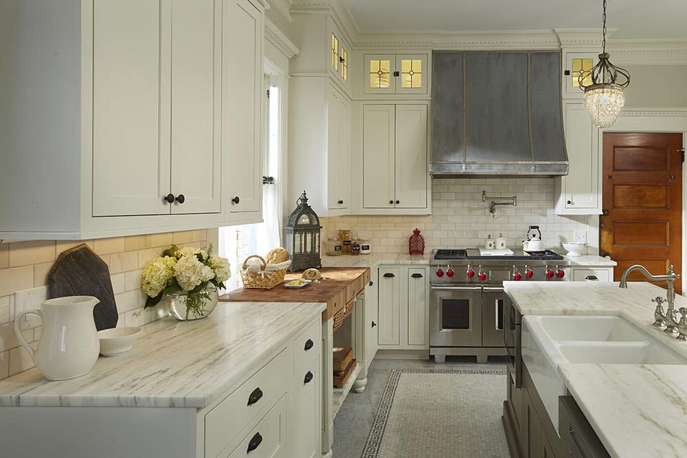 kitchen has white shaker inset cabinets, custom butcher block pastry center, apron sink, professional gas range and custom range hood and glass door cabinets