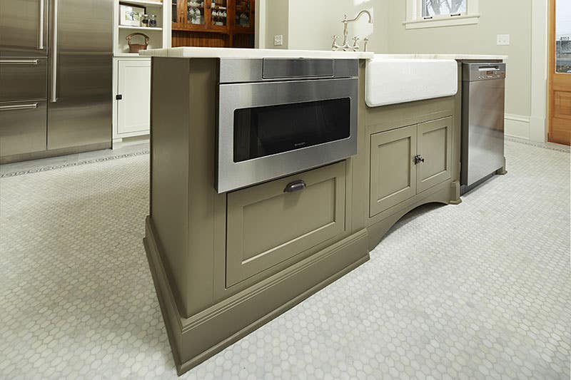 island built of painted green tea leaf cabinets has microwave drawer, porcelain apron sink and dishwasher