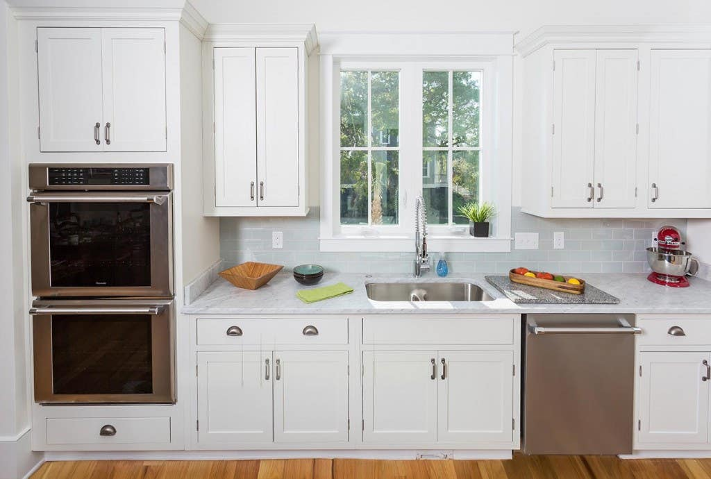 Kitchen in new luxury home, viewed facing the window over the sink, shows timeless inset cabinets finished with broad crown molding, white marble countertops and pale gray subway tile backsplash