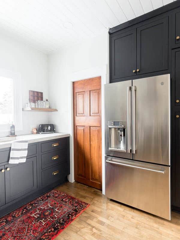 CliqStudios Austin inset cabinets in Carbon black paint frame the refrigerator to create a built-in look