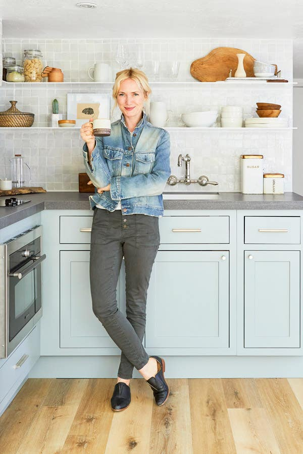 interior designer Emily Henderson standing in front the small kitchen she designed with CliqStudios Austin cabinets in Harbor