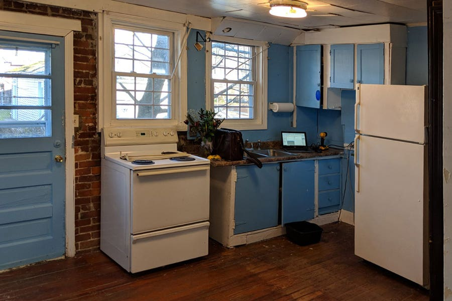 neglected old kitchen will blue cabinets that are falling apart