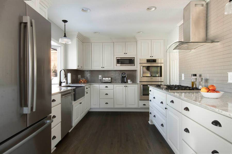 A kitchen using CliqStudios Carlton cabinets in White with dark floors.