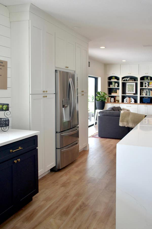 CLiqStudios Dayton cabinets in white, and in the center is a refrigerator. Next to it, base Dayton cabinets are in Carbon with white countertop.