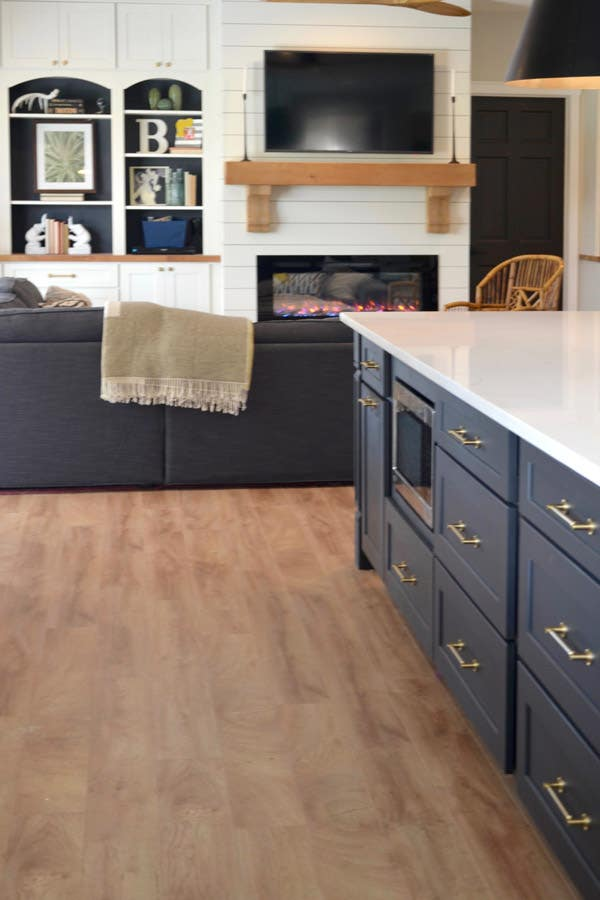 CliqStudios Dayton cabinets in Carbon used in an island with a white countertop. Behind that is a sitting area using CliqStudios Dayton cabinets in white for storage.