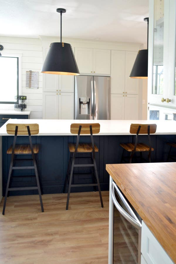 CliqStudios Dayton cabinets in carbon at the island and white for the wall cabinets. The island has a white waterfall countertop and tall bar chairs pulled up, with pendant lighting with black shades hanging above. Behind that is a wall of white cabinets, and in the center is a fridge.