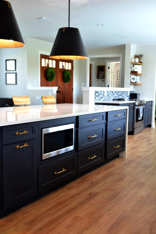 CliqStudios Dayton cabinets in Carbon used in a kitchen island with a white waterfall countertop. A base microwave sits in the center of the island, and pendant lighting with black shades hang above.