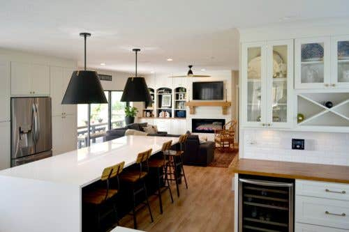 Full view of a kitchen using CliqStudios Dayton cabinets in Carbon and White. In the focus of the photo is a white butler's pantry and the island, with a white waterfall countertop.