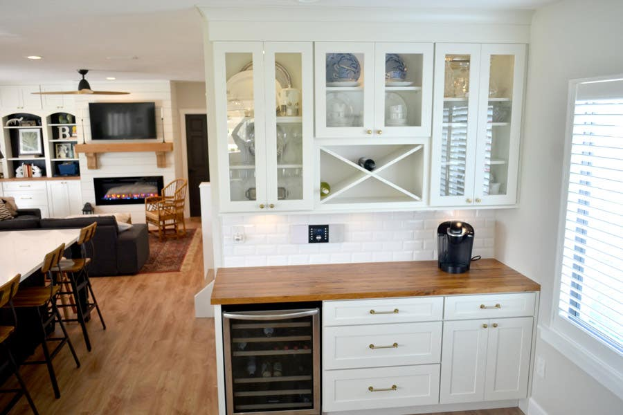 CliqStudios Dayton cabinets in white forming a butler's pantry, with a wine cooler in the base and a wine rack above centered in glass faced cabinets.