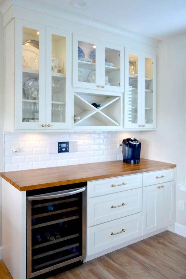 CliqStudios Dayton cabinets in White used in a butler's pantry, complete with a wine cooler and rack, a butcher block counter, and glass cabinets.