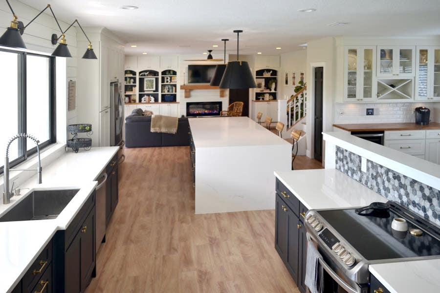 Full view of a two-toned kitchen using CliqStudios Dayton cabinets in Carbon and White. The countertops are white and butcherblock.