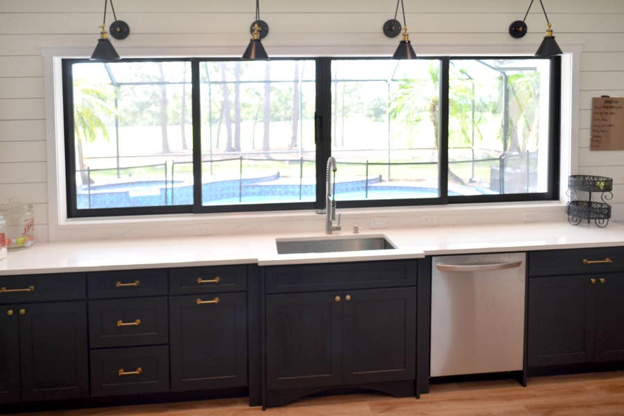 Living area using CliqStudios Dayton cabinets in White around the entertainment area for added storage. Base cabinets have butcher board countertops,, above them is open air shelving, and flush with the ceiling are more small cabinets.