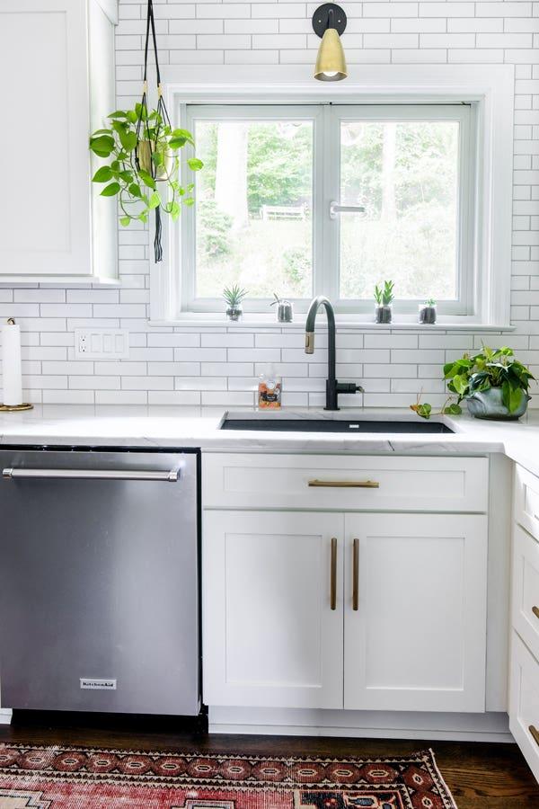 Kitchen corner with CliqStudios white Dayton cabinets, dark sink, and stainless-steel washing machine.