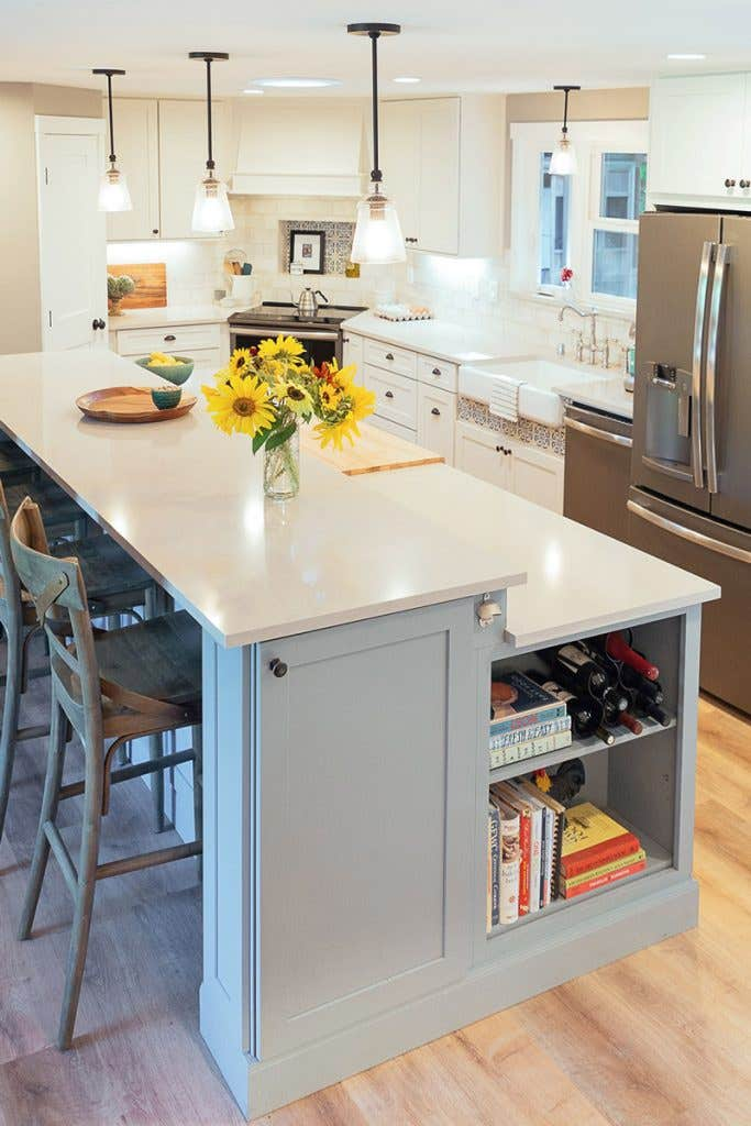White kitchen with large two-tier blue island, stainless appliances and corner range