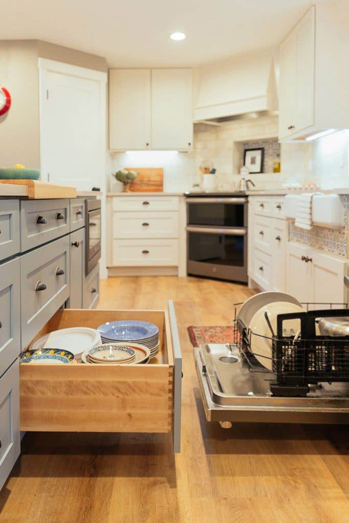 Open dishwasher and dish storage door open in white and blue kitchen