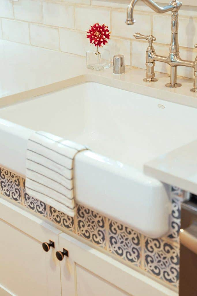 White apron sink with blue tile detail below the front skirt