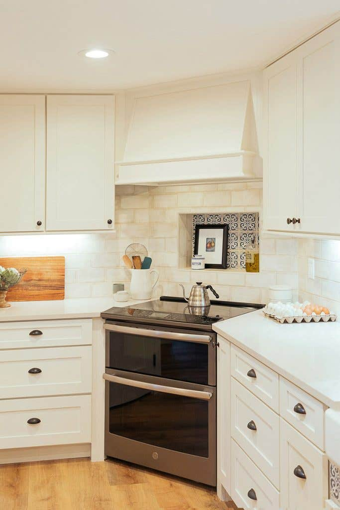 Stainless steel range in the corner of a kitchen with white cabinets and range hood