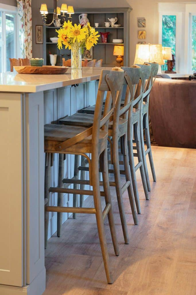 Four chairs at a blue kitchen island facing toward the living room
