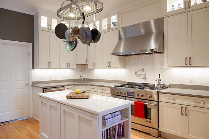 remodeled kitchen has ceiling height lighted glass door cabinets, a professional six-burner range and stainless hood, island with open shelving and decorative crown molding