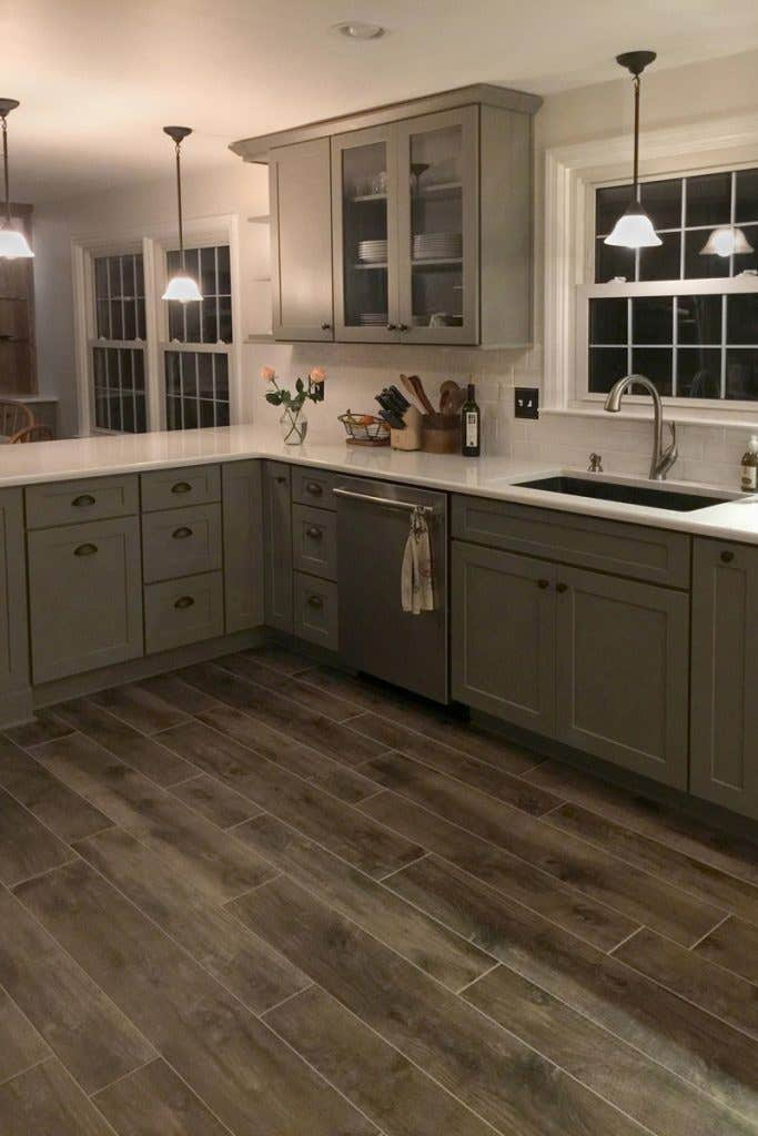 Gray kitchen cabinets and pull-out storage surround the kitchen sink