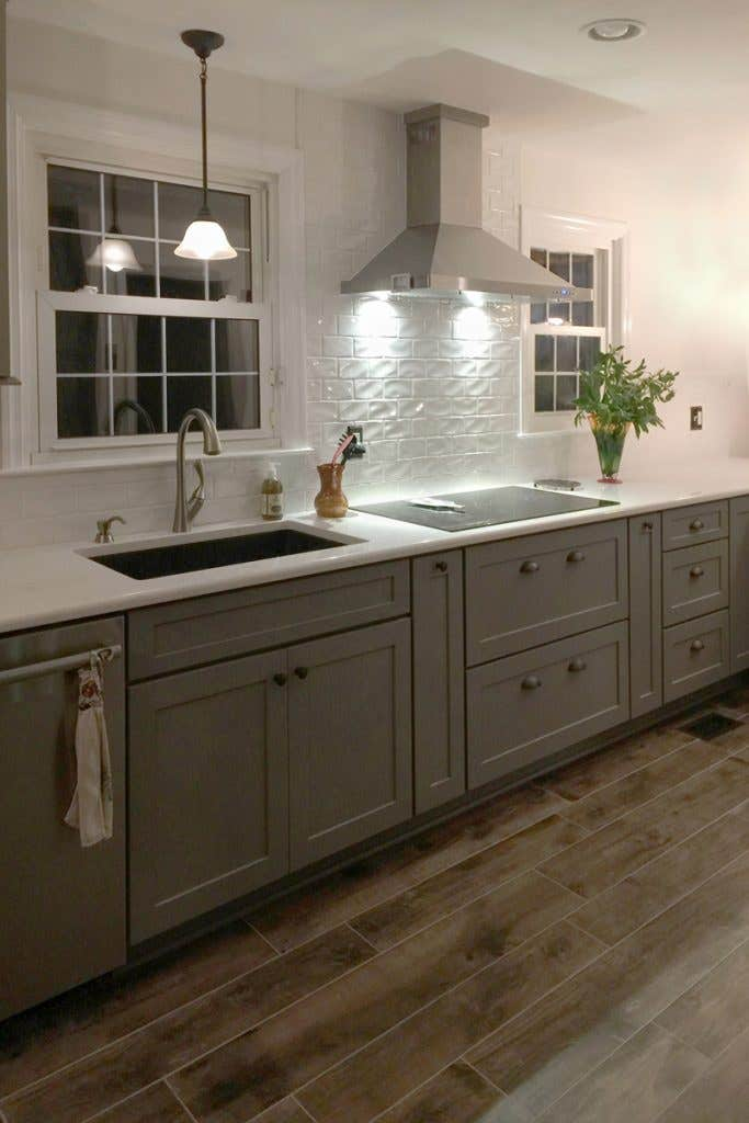 Cooktop with stainless hood, white backsplash and gray storage cabinets below