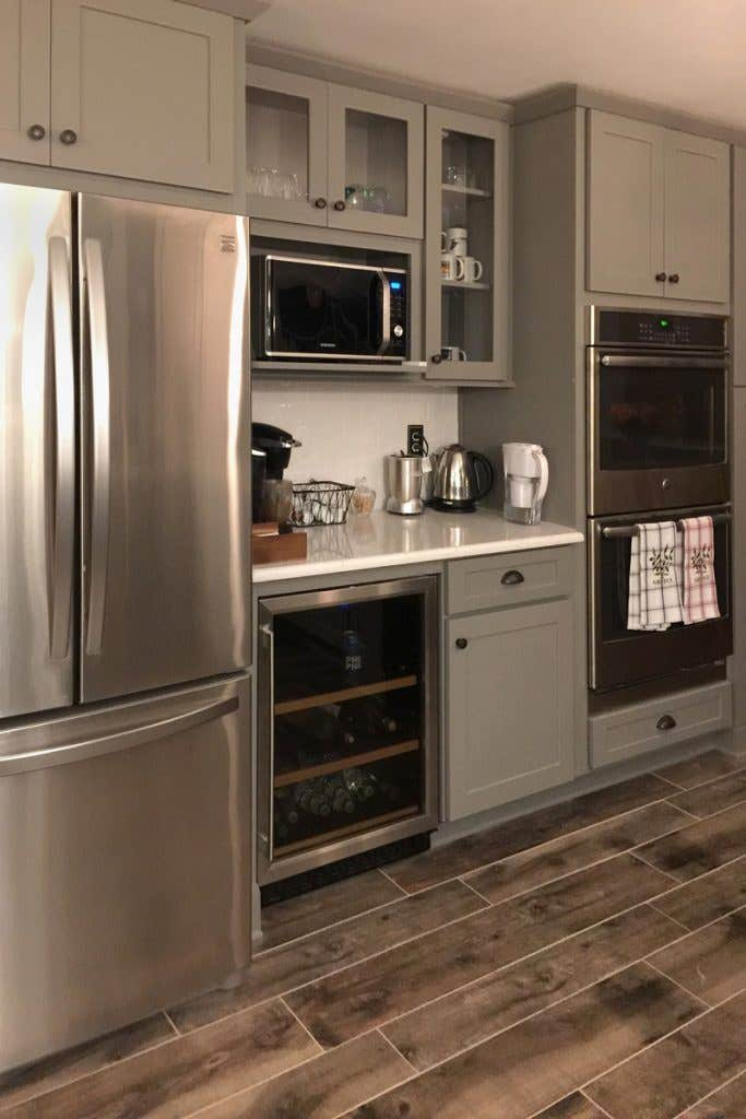 Kitchen beverage center with gray cabinets, wine fridge and glass front cabinets