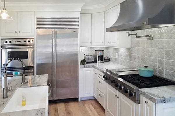 Corner of kitchen with white cabinets, high-end stainless steel appliances and white apron sink in island