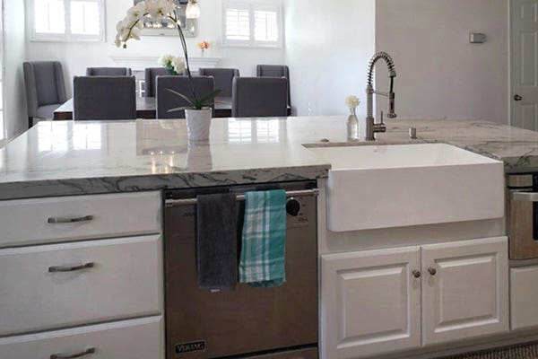 Kitchen island with white cabinets, dishwasher, apron sink and microwave facing the formal dining room