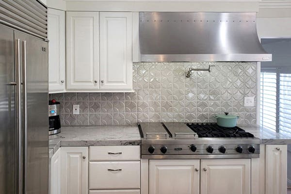 Stainless steel cooktop with matching range hood, wall faucet, grey tile backsplash and white cabinets
