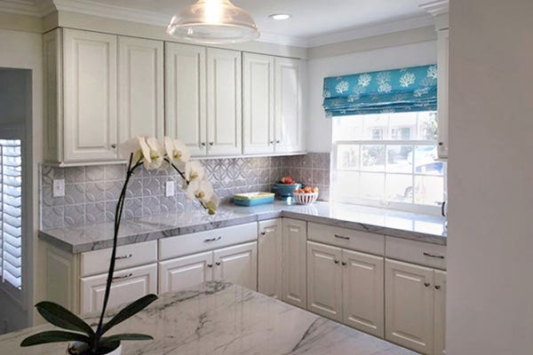 Corner of kitchen with white Bayport cabinets, gray tile backsplash and a window