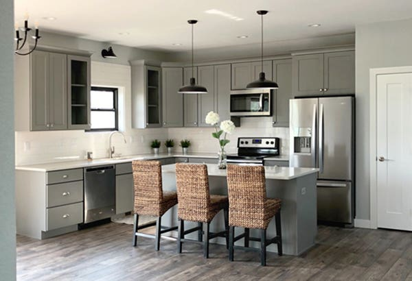 open l-shaped kitchen with island seating, gray kitchen cabinets and black light fixtures