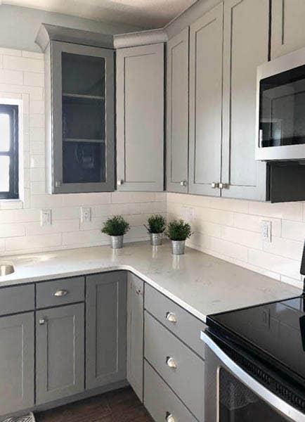 Glass kitchen cabinet doors in studio gray surround kitchen sink