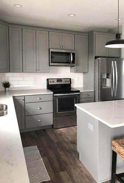 Studio gray kitchen cabinets with subway tile backsplash, stainless appliances and white countertops
