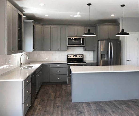 Open kitchen with island, gray cabinets, white countertops and subway tile backsplash