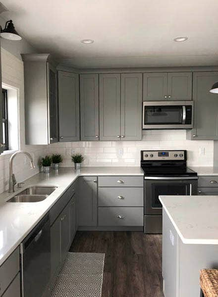 Gray Shaker cabinets surrounded by white countertops and backsplash with undermount sink and stainless appliances.
