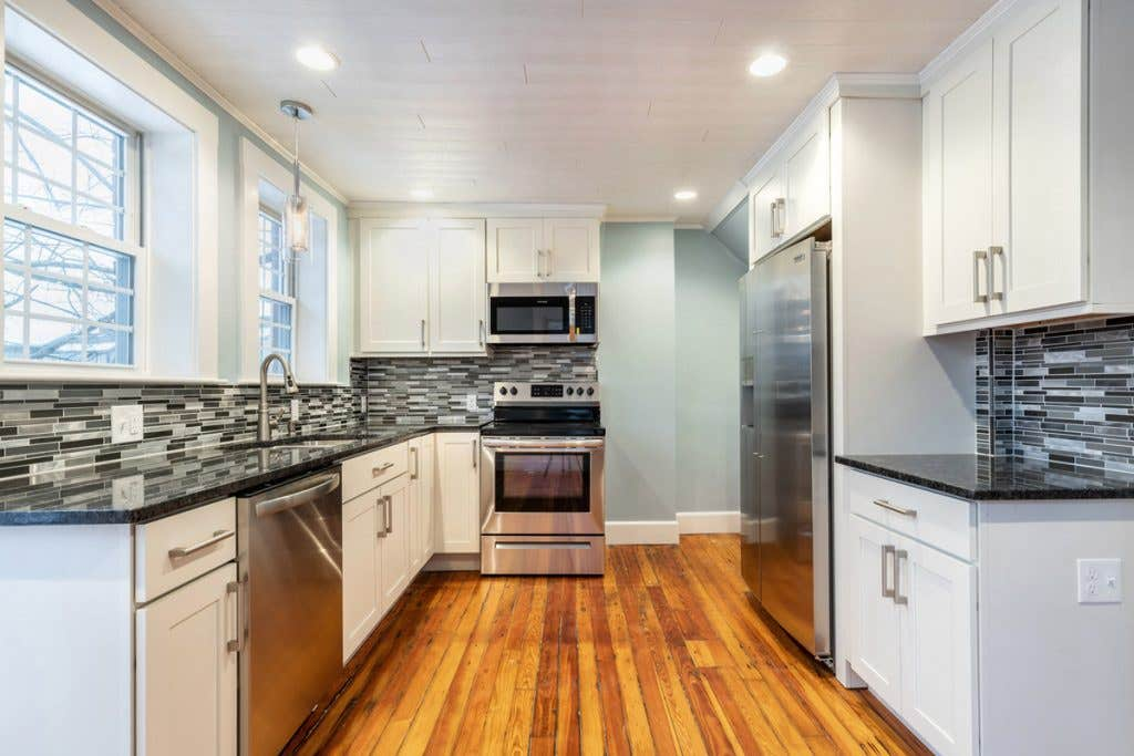 small u-shaped kitchen with white cabinets, light blue walls, black countertops and original wood floors