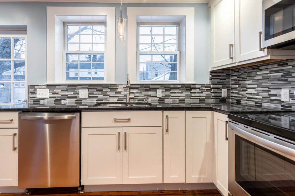 Kitchen sink facing two windows with white Shaker cabinets and black and white backsplash