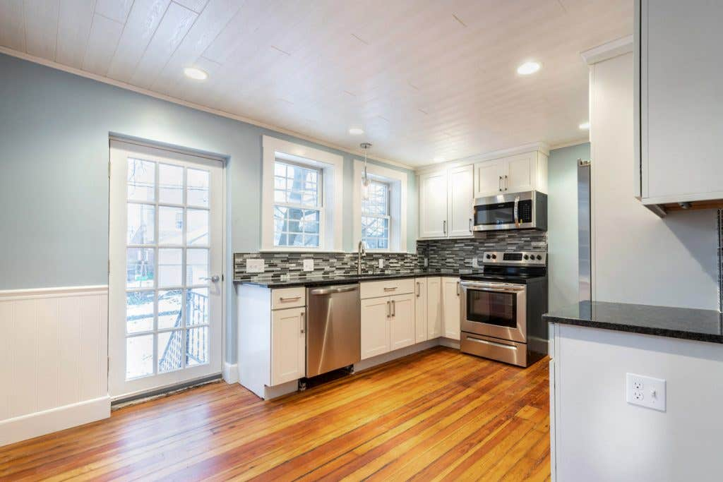 updated kitchen with white cabinets and stainless appliance, with original hardwood floors