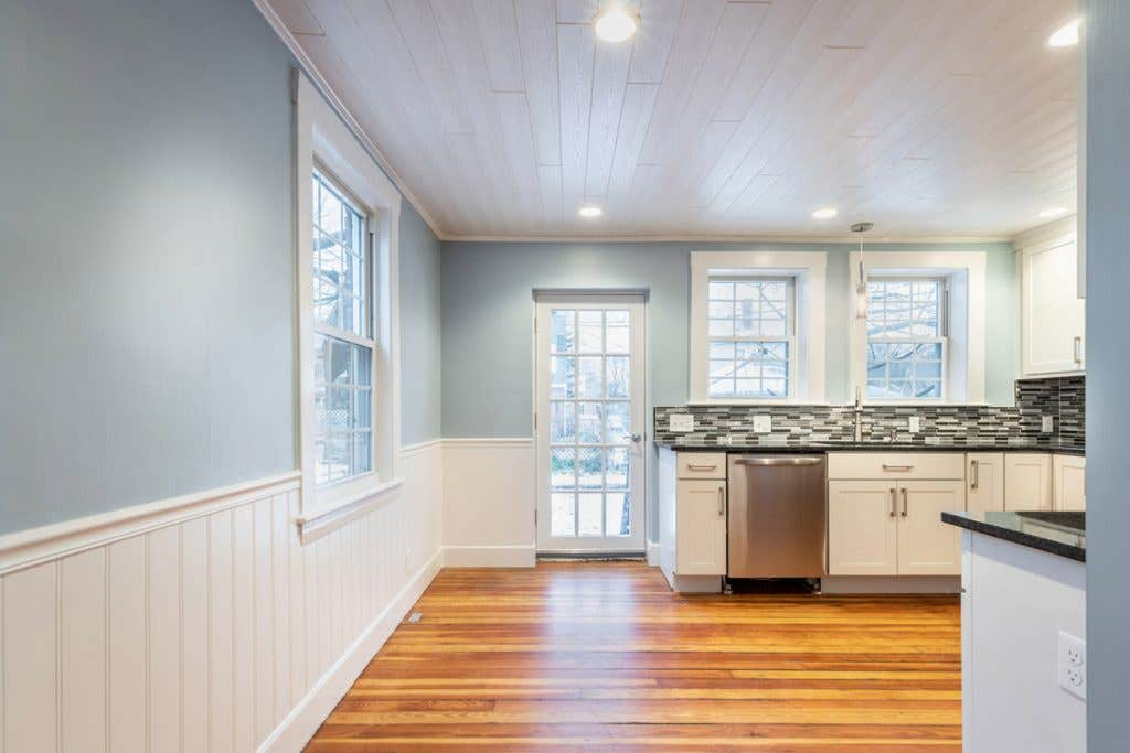Kitchen with white cabinets and small eat-in dining area near back door