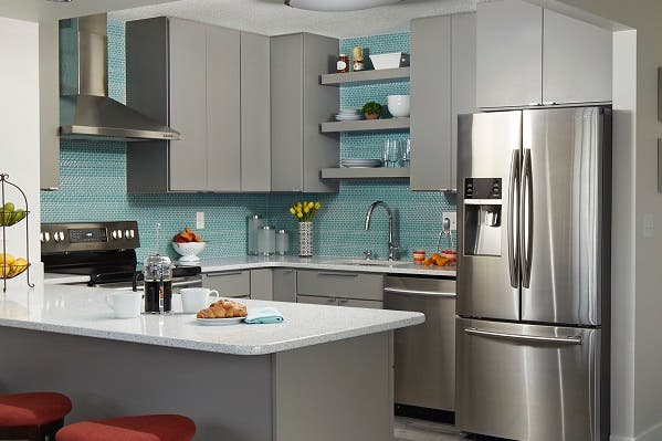 corner view of condo kitchen with gray slab door cabinets, ceiling high aqua glass mosaic tiles, stainless range hood and floating shelves