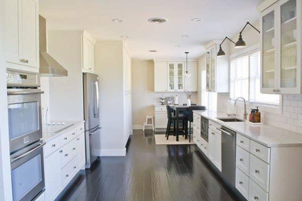 galley kitchen with white cabinets and dark hardwood floor