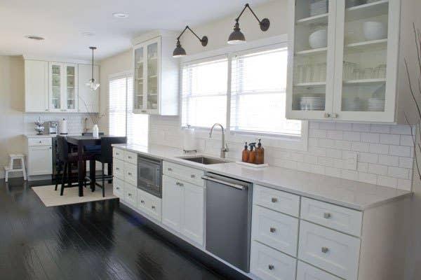 white kitchen cabinets with glass doors and white subway tile backsplash.