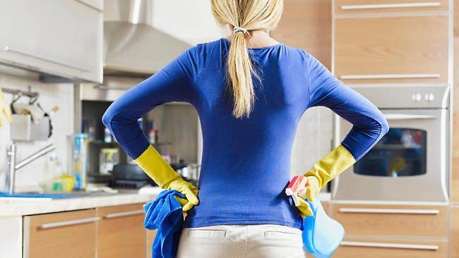 Woman surveying the kitchen while cleaning