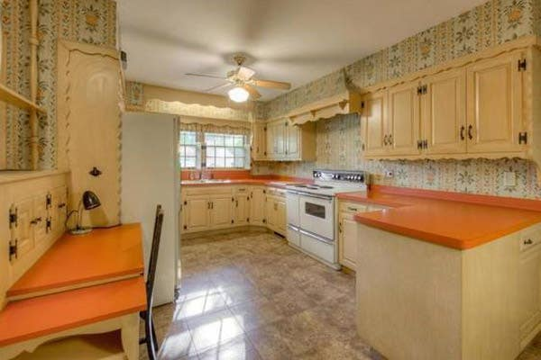 outdated kitchen with flower wallpaper, yellowed cabinets and orange countertops