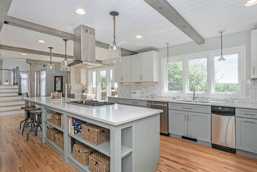 open gray kitchen island using voided doors for storage space.
