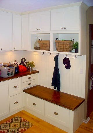 laundry room locker zone created with white shaker cabinets and beadboard wall