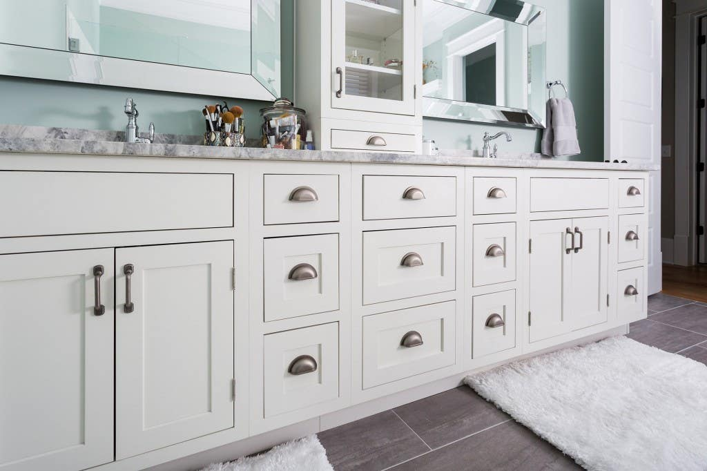 Deluxe new home features double vanity built from classic inset cabinets. Bathroom has dual custom mirrors, glass-front cabinet and drawer stacked on counter, and porcelain tile floor